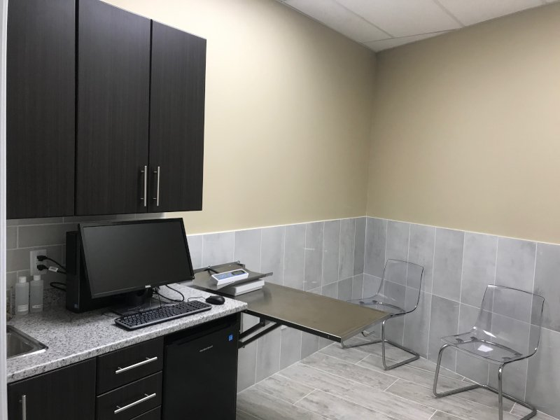 The exam room with cabinets, seating and an exam table